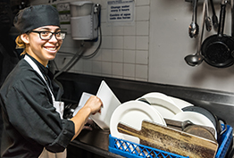 Young woman in dishroom smiling and doing dishes